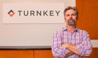 Co-Founder of TurnKey, John Banczak standing in front of TurnKey logo